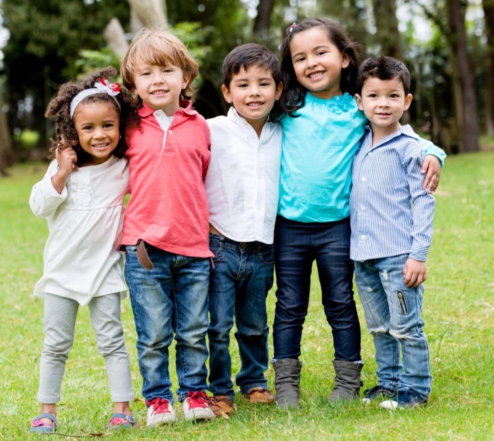 Group of small children arms around each other