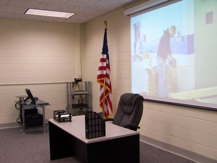 The front of a classroom with a projection screen against the wall and a desk with a chair in front of it. There is an American flag next to the desk.
