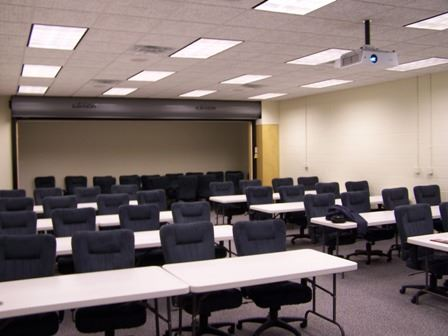 A classroom setting with a projector and tables and chairs set up.