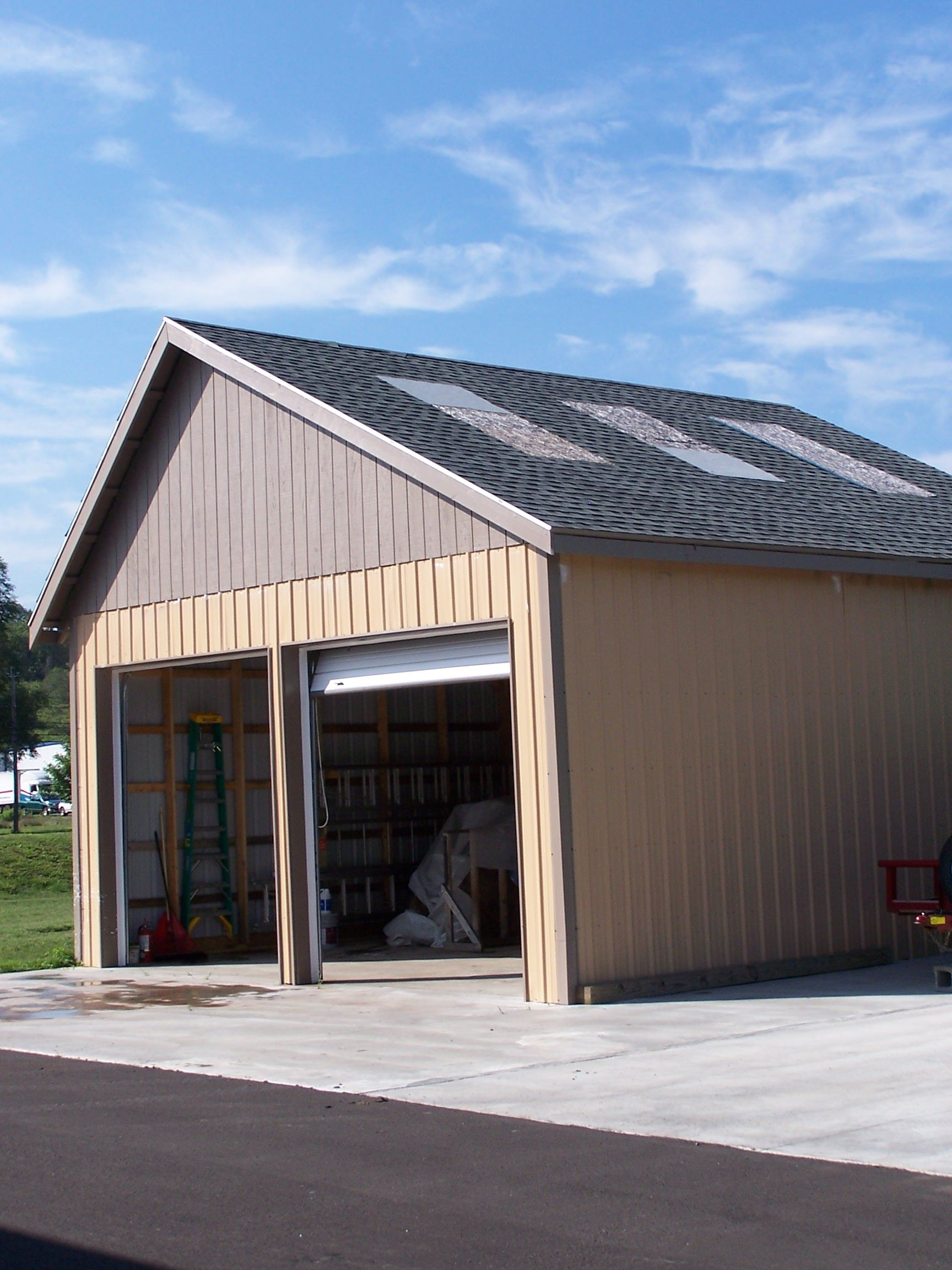 A building with two garage openings and a dual pitch roof vent simulator.