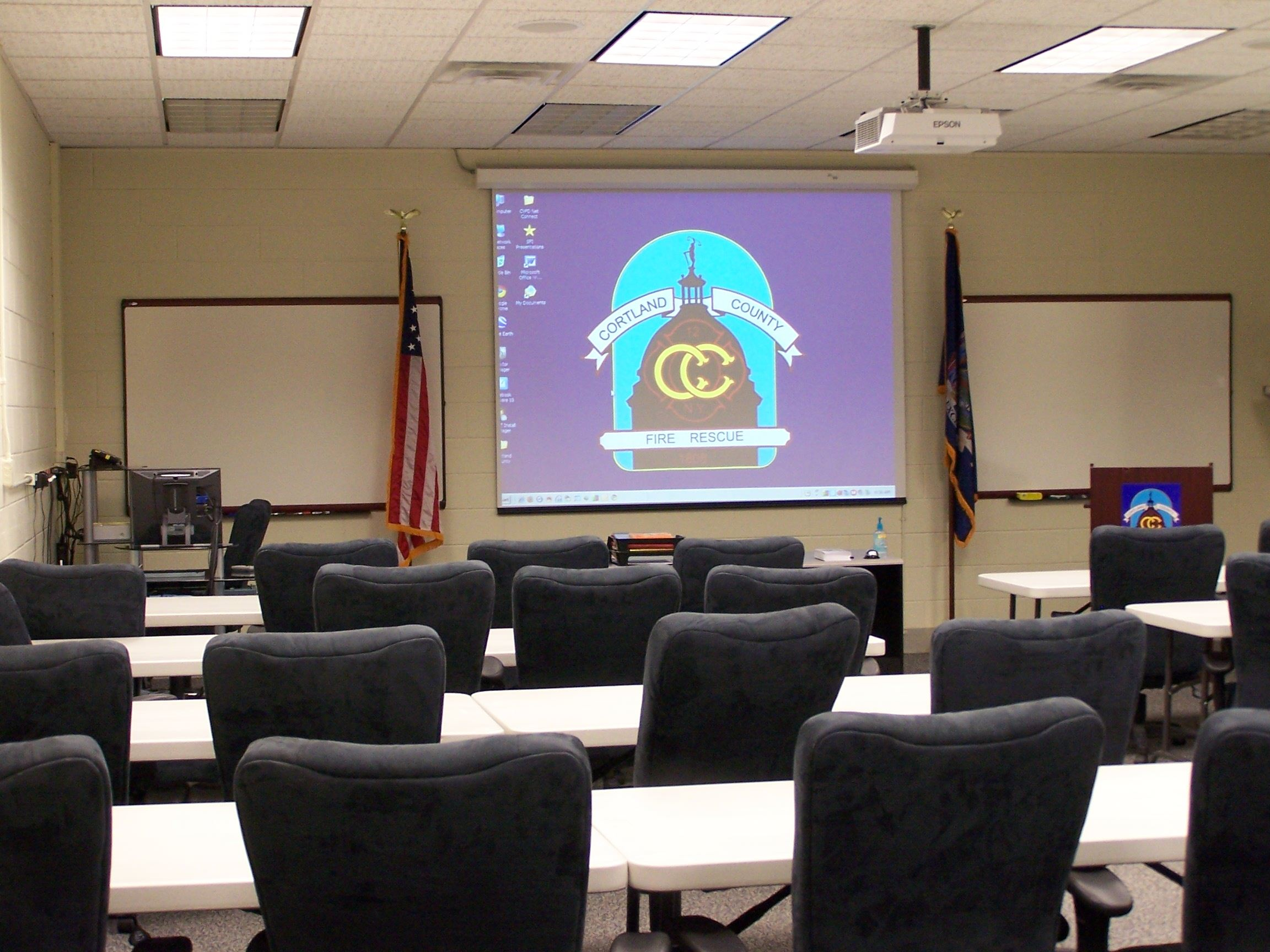 A classroom setting with tables and chairs facing the front on the room with the Cortland County Fire Rescue logo.