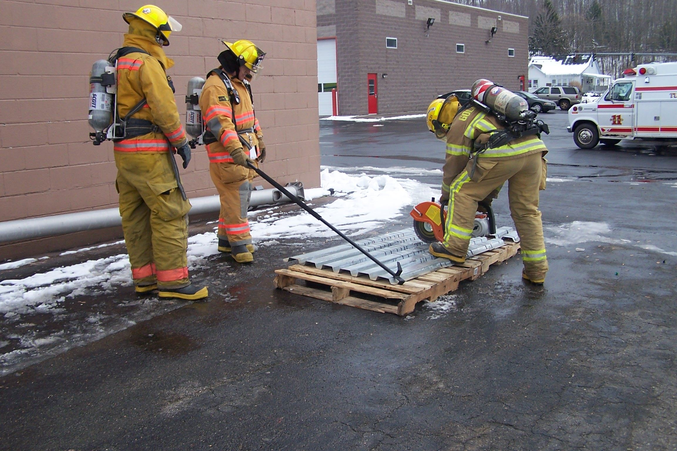 A firefighter practices cutting a metal roof with a powersaw while another firefighter holds the roof piece down on top of a pallet. A third firefighter stands by and observes.