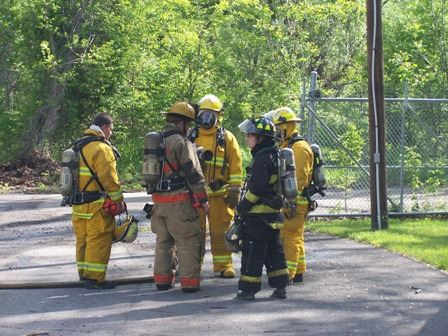A group of five firefighters stand in a huddle.