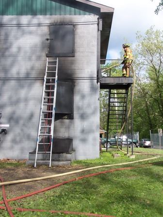 The back of a training facility with a ladder against it. A firefighter is standing on the top of a side staircase holding a hose.