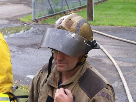 A firefighter wearing a helmet with a shield.