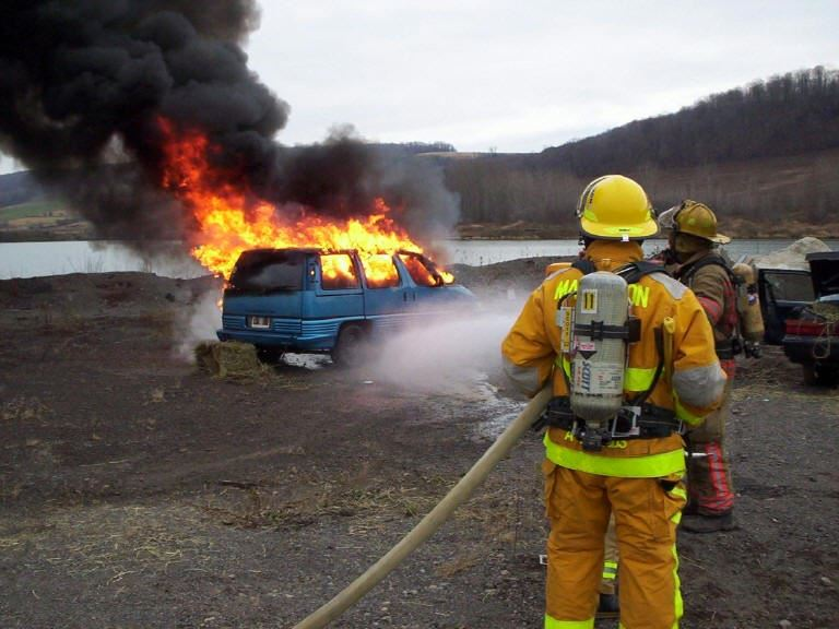 Two firefighters holding a hose and spraying down a blazing car fire.