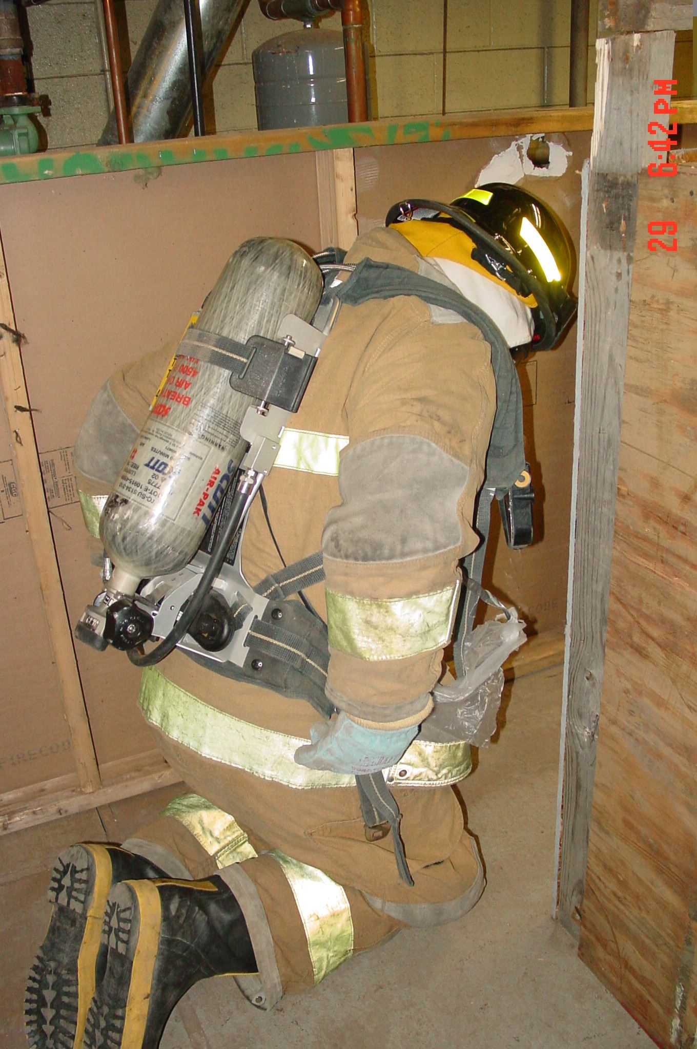 A firefighter kneeling down on his knees during a training exercise.